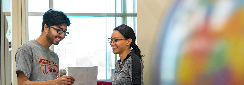 Admissions Representative Wahidah Aziz helping graduate student at orientation